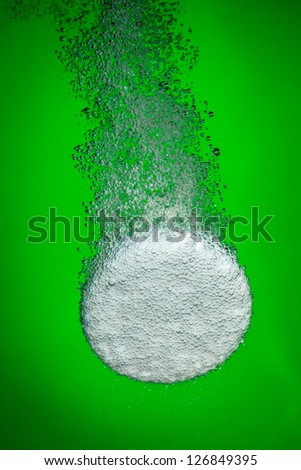 Effervescent tablet in water with bubbles on a green background - stock photo