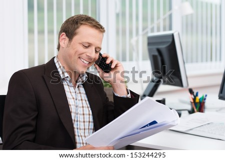 Efficient businessman answering a phone call at the office to discuss a document that he is holding in his hand - stock photo