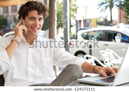 Efficient businessman making a call on his smart phone and using a laptop computer while sitting at a coffee shop terrace table, outdoors. - stock photo