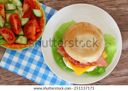 Egg and bacon muffin with green salad  - stock photo