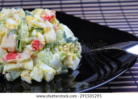 Egg and crab meat salad on a black plate, shallow focus - stock photo