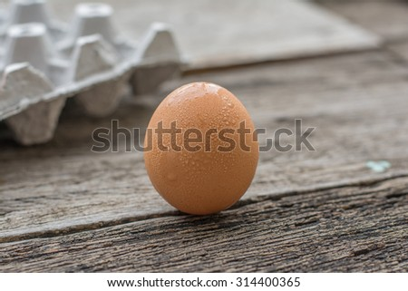 egg and egg carton on wooden background - stock photo