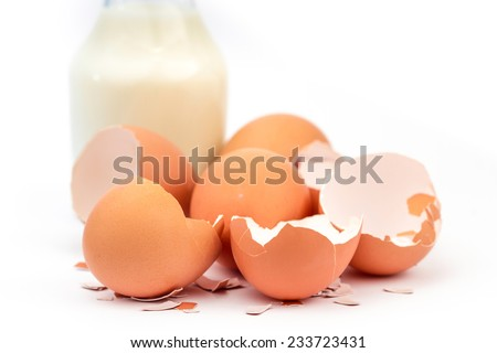 egg and eggshells with a bottle of milk.