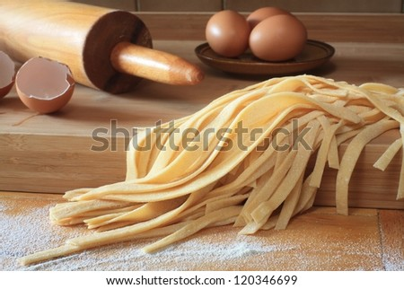 Egg and homemade noodles  on wooden table - stock photo