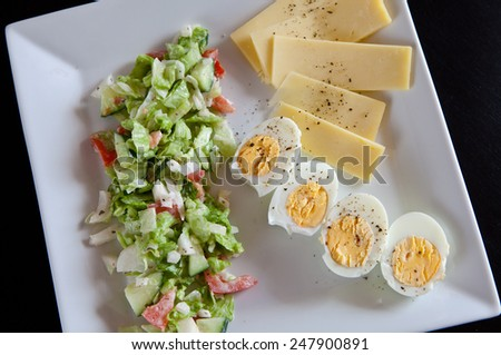 Egg and salad with backed duck, rucola, cherry tomatoes, mozzarella and corn. - stock photo