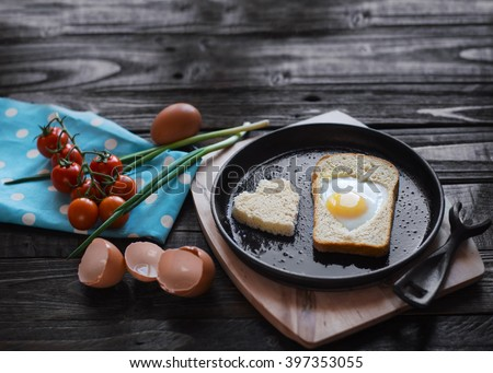 Egg baked in a bread in a heart shape on a cast iron skillet. Fried eggs, toast, cherry tomatoes, green onions on dark wooden background .. A full breakfast in a rustic style. - stock photo