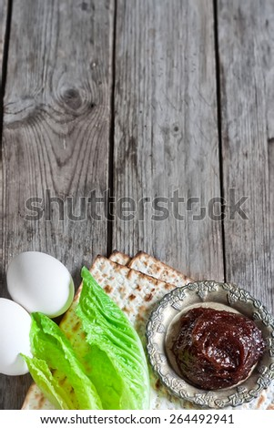 Egg, bitter salad leaves, matzot and haroset - traditional jewish passover celebration elements. Copy space background. - stock photo