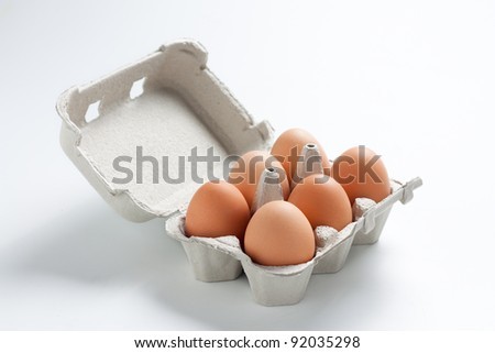 Egg box full. Cardboard box with brown eggs - stock photo
