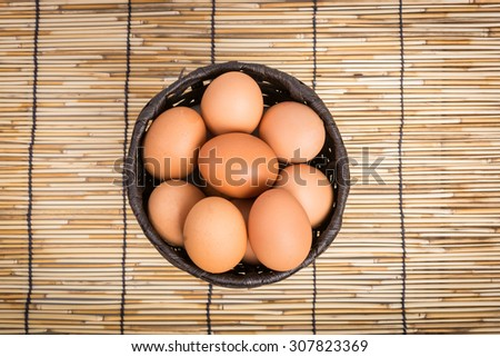 Egg collection in the basket on wooden background - stock photo