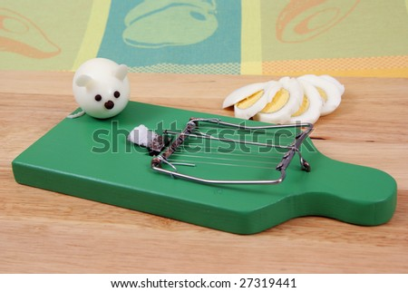 egg cutter as mousetrap and egg-mouse as background