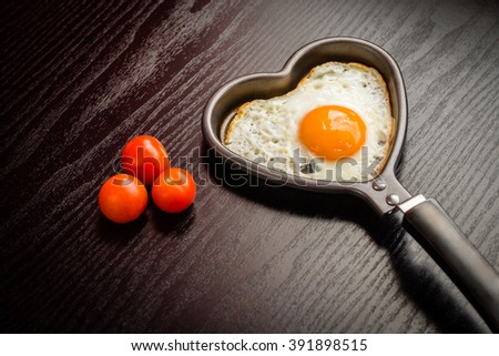 Egg, fried egg, egg in the shape of a heart, egg in a frying pan, egg and cherry tomatoes  - stock photo