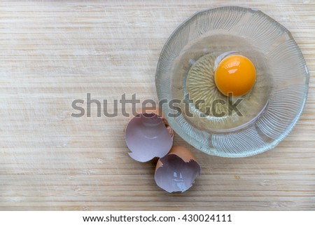 Egg in a bowl on the wooden chopping board and egg shell by side ready to be cooked a delicious egg meal - stock photo