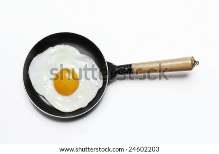 Egg in a frying pan. Frying egg on a pan. - stock photo