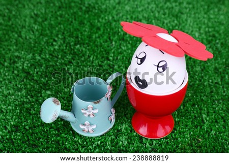 Egg in egg cup with watering can on green background - stock photo