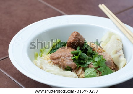 Egg noodle with delicious stewed pork and dumpling in white bowl, closed up. - stock photo