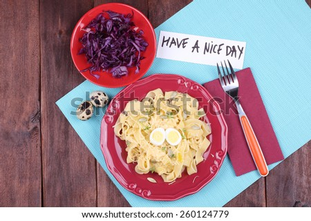 Egg noodles with eggs quail. Italian pasta with cheese and watercress salad. Salad of red cabbage. A delicious and hearty lunch. Tableware, top view. - stock photo