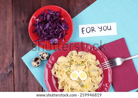 Egg pasta with quail egg, watercress salad and seeds. Dish pasta and coleslaw on the table. Delicious hearty lunch. Surprise for dear person. Top view. Pasta dish. - stock photo