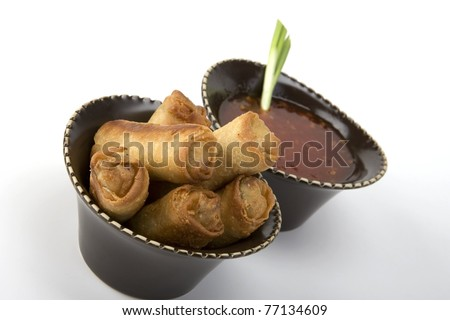 Egg rolls and sweet and sour sauce in a ceramic bowl - stock photo