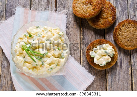Egg salad with chives on a wooden background. Selective focus. - stock photo