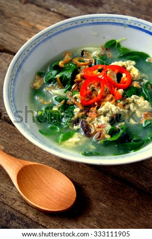 Egg soup with vegetables Asian Style on wooden background