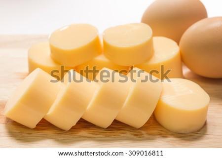 Egg tofu sliced on wooden cutting board - stock photo