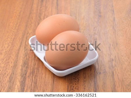 Egg. Top view of white bowl with egg on wooden background. - stock photo