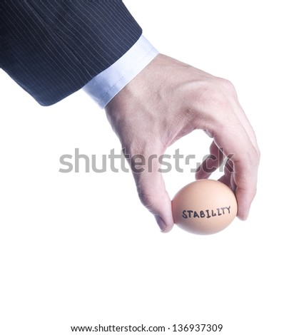 Egg with inscription Stability between fingers. Concept of the crisis. Isolated over white