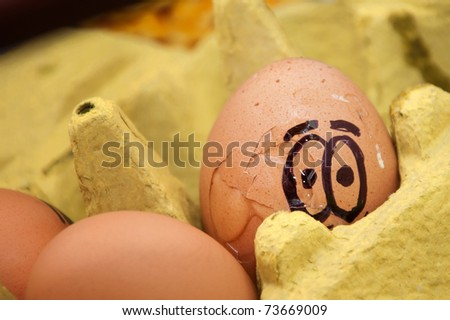 Egg with scared face in a cardboard egg carton - stock photo