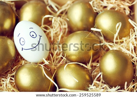 Egg with smiley face among golden eggs - stock photo
