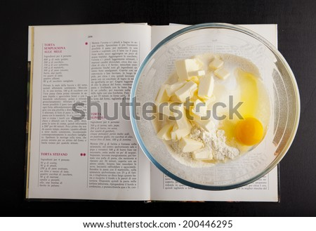 egg yolk, flour and butter. cooking ingredients in a glass bowl. ready for mixing dough. cookbook. dark background. isolated. - stock photo