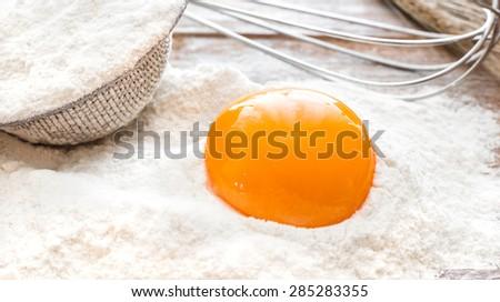 Egg yolk in flour on a wooden board - stock photo