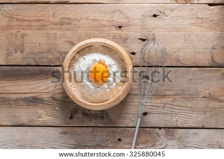 Egg yolk in the flour and whip for beating on wood table. Top view. - stock photo