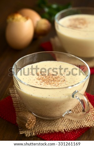 Eggnog drink in glass cups sprinkled with ground nutmeg, eggnog cake baked in eggshell in the back, photographed on dark wood with natural light (Selective Focus, Focus  in the middle of the eggnog)