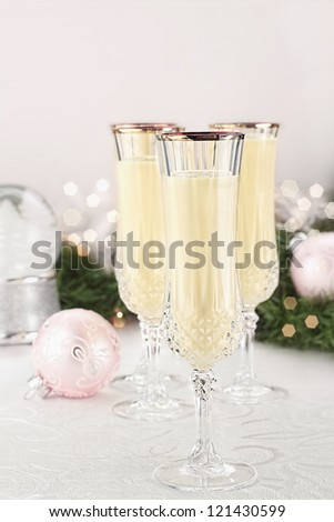 Eggnog in fluted crystal glasses with Christmas decor in the background. Shallow depth of field with selective focus on glass in foreground. - stock photo