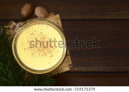 Eggnog with freshly grated nutmeg on the top, photographed overhead on dark wood with natural light (Selective Focus, Focus on the top of the eggnog)