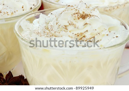 Eggnog with whipped cream and spices. Selective focus with some blur on lower portion of image. - stock photo