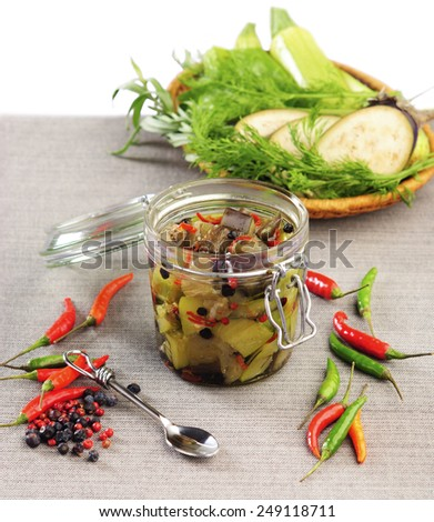eggplant and zucchini canned pepper herbs in a glass jar on a gray napkin - stock photo
