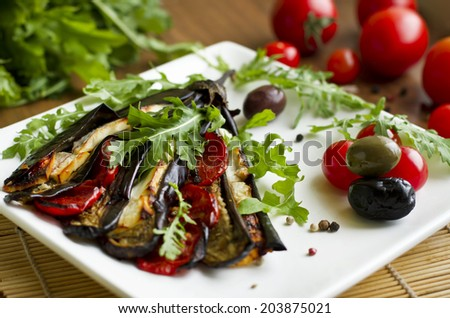 Eggplant grilled with tofu cheese, herbs and tomatoes - vegan food - stock photo