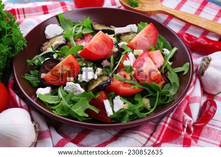 Eggplant salad with tomatoes, arugula and feta cheese, on napkin, on color wooden background - stock photo