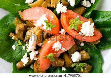 Eggplant salad with tomatoes, feta cheese, spinach and greens