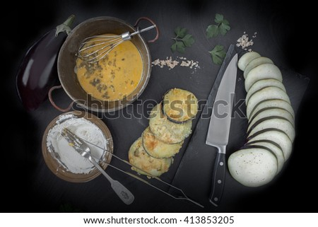 Eggplant slices, raw and fried, ingredients for the preparation of parmigiana, a traditional recipe of the Italian cuisine. Top view shot. - stock photo