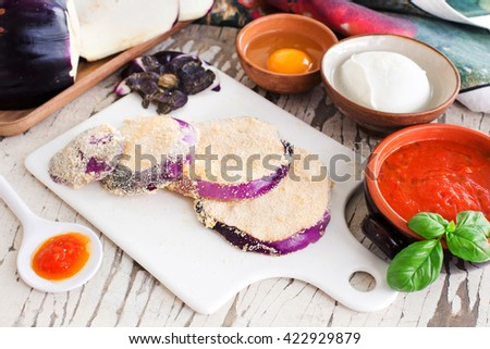 eggplant slices with breadcrumbs and other ingredients for parmigiana - stock photo