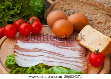 Eggs and bacon with cheese, tomato and green salad