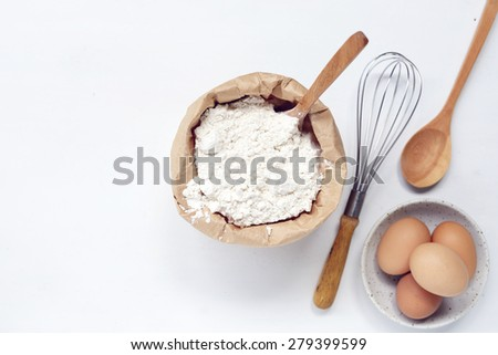 eggs and flour on white table background. basic baking background. - stock photo
