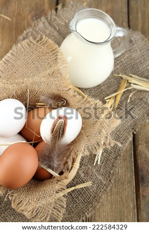 Eggs and fresh milk in glass jug, on wooden background. Organic products concept - stock photo