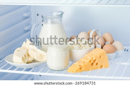 eggs and tasty healthy dairy products in the refrigerator: sour cream in the bank, cottage cheese in  bowl, eggs, cheese, butter on a saucer and milk in a jar - stock photo