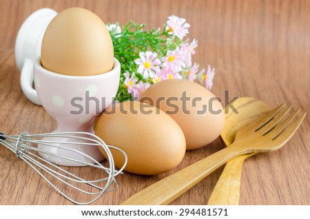 Eggs and wooden spoon with flower on wooden background. - stock photo