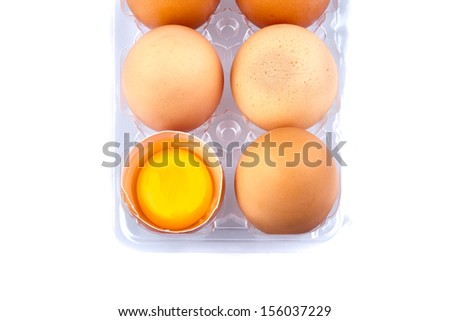 Eggs and yolk in a plastic transparent package on white background - stock photo