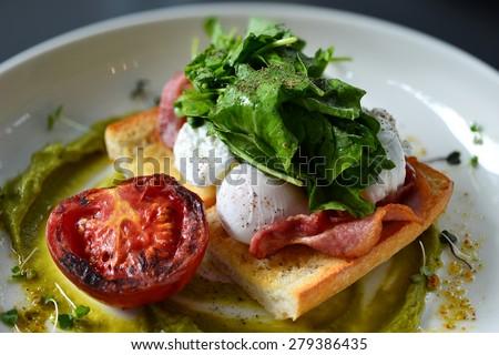 eggs benedict breakfast bacon poached egg, potato and salad - stock photo