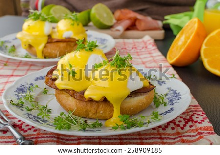 Eggs benedict, prosciutto topped with Hollandaise sauce - stock photo